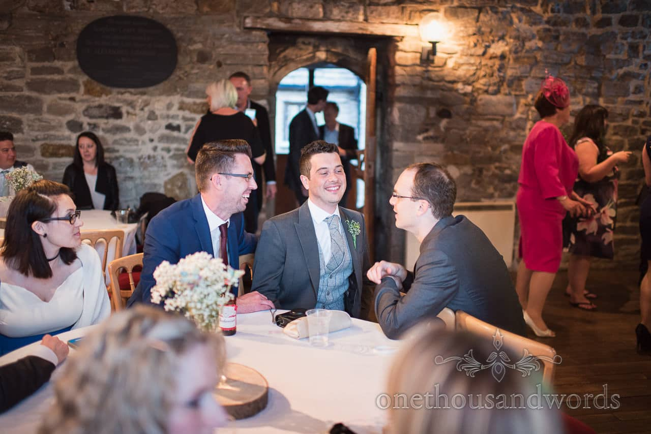 Groom shares a joke with guests at Scaplens court wedding photographs