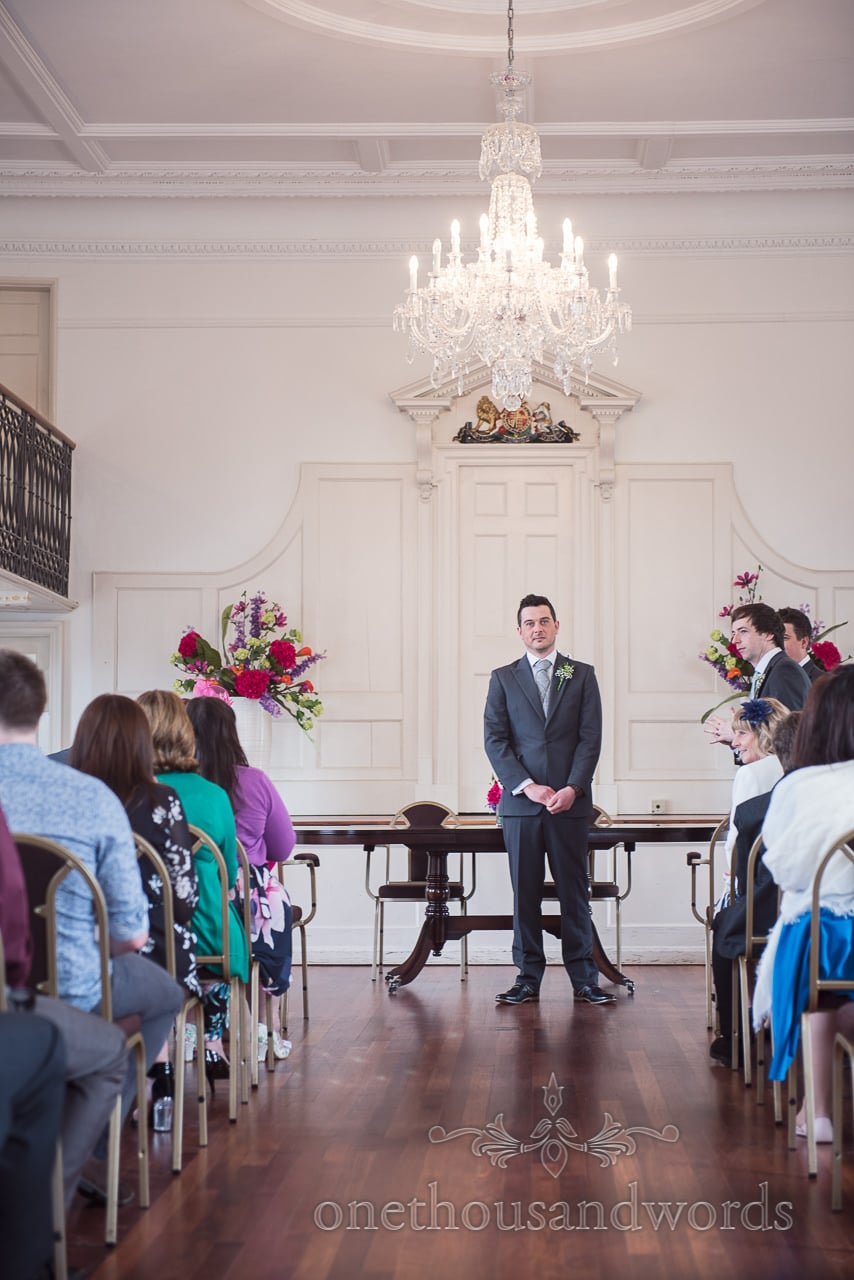 Groom waits for his bride at Poole guildhall wedding photographs