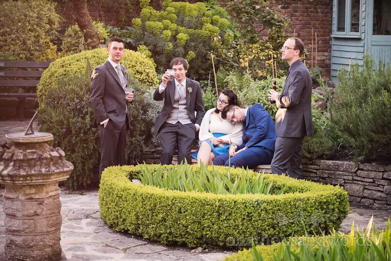 Groom with friends in garden at Scaplens court wedding photographs