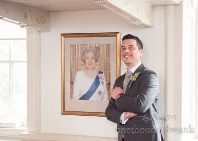 Groom with portrait of the Queen at Poole guildhall wedding photographs