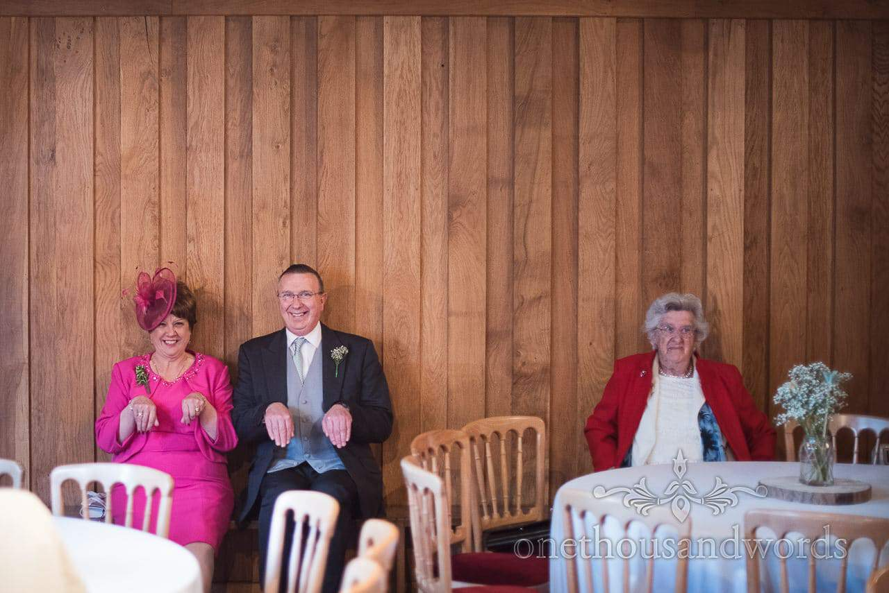 Grooms parents pose for the camera at Scaplens court wedding photographs