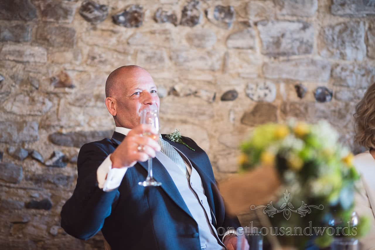 Guest raises a glass at Scaplens Court wedding photographs