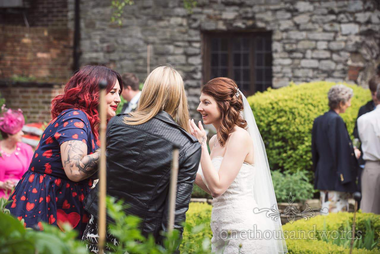 Guests and the bride in the garden at Scaplens court wedding photographs