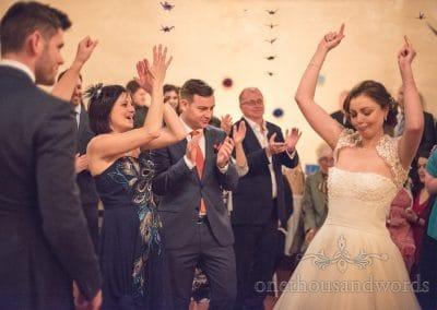 Guests applaud brides dancing at Walton Castle wedding photographs