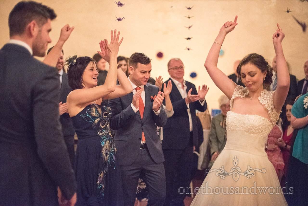 Guests applaud happy bride's dancing on dance floor