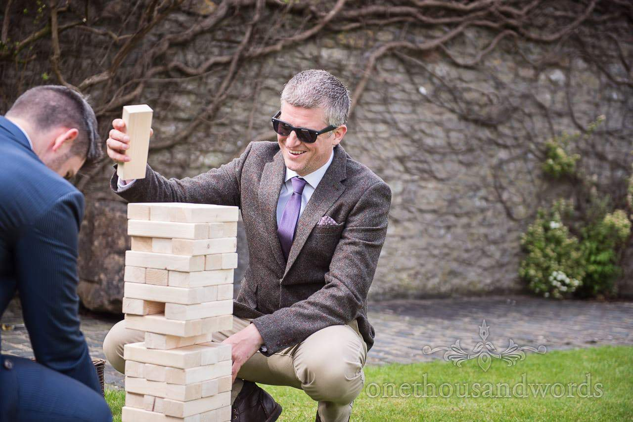 Guests playing lawn Jenga at Walton Castle wedding photographs