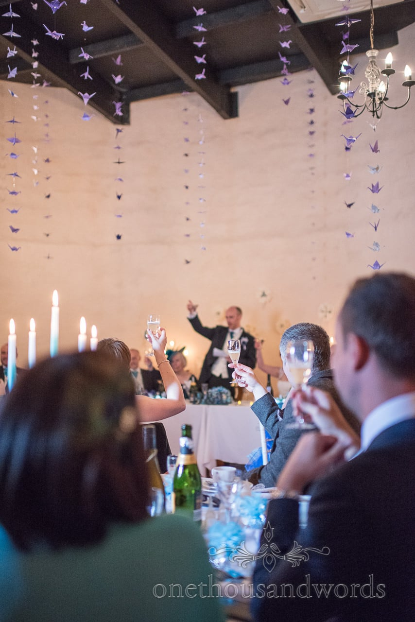 Guests raise glasses to toast at Walton Castle wedding photographs