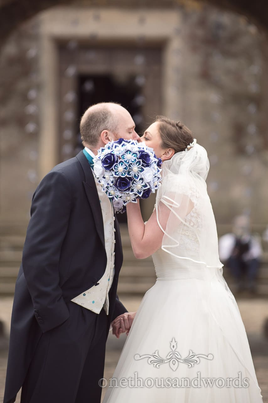 Kiss behind bouquet at Walton Castle wedding photographs