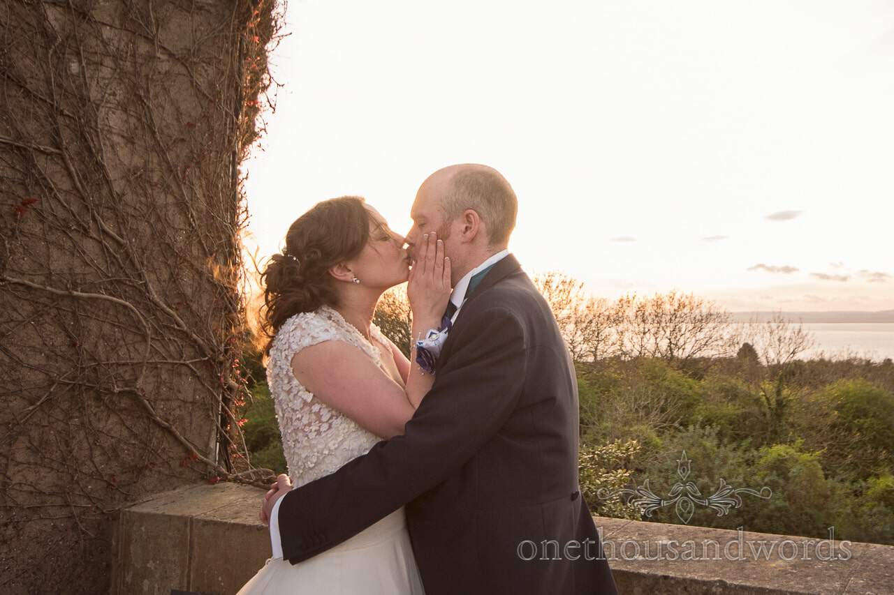 Bride and groom kiss on a balcony overlooking the Bristol channel