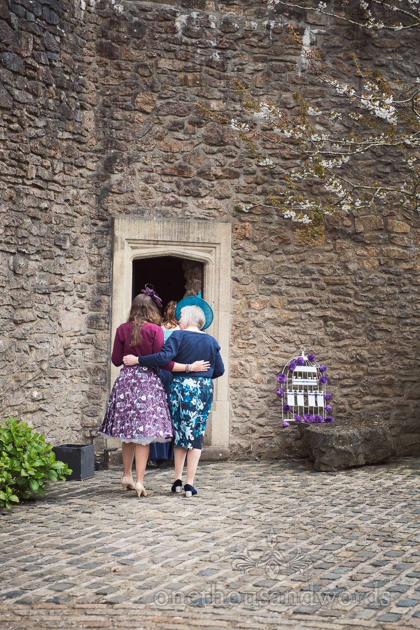 Maid of honor and mother of the groom enter turret for wedding breakfast at Walton Castle wedding photographs