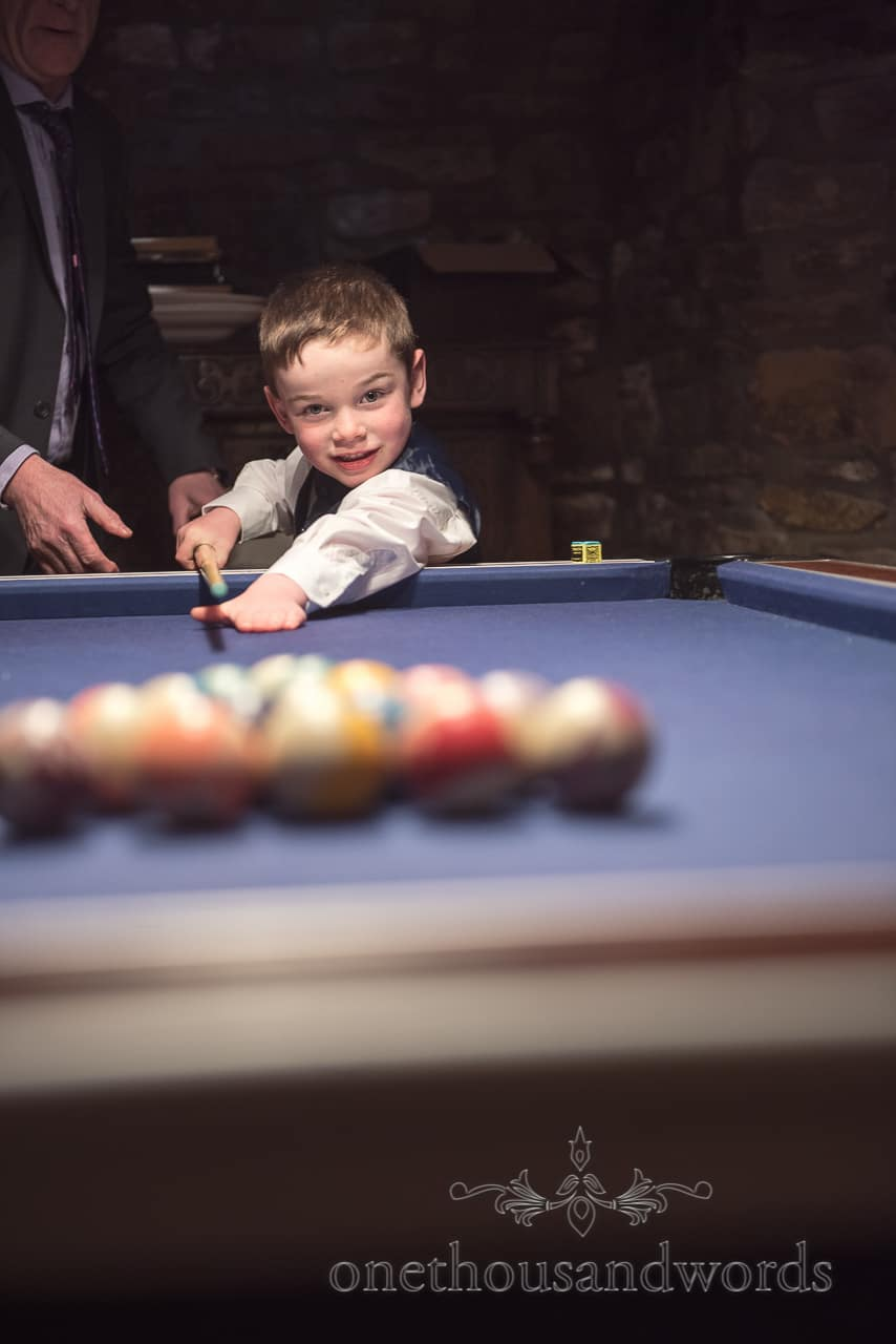 Page boy at pool table at Walton Castle wedding photographs