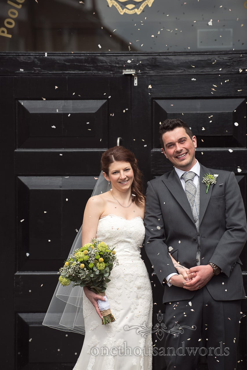The bride and groom are showered with confetti at Scaplens Court wedding photographs