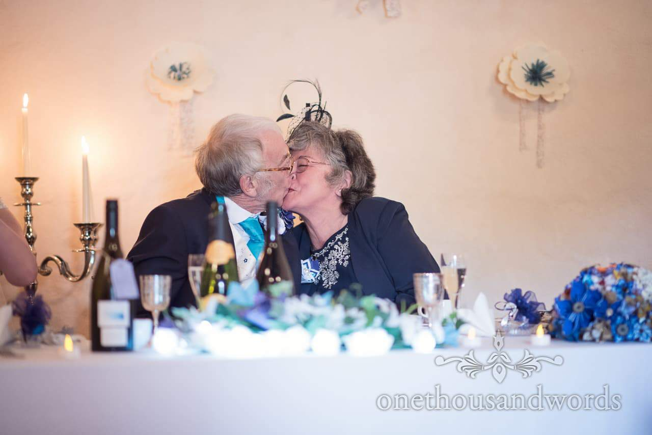 Top table kiss during speeches at Walton Castle wedding photographs