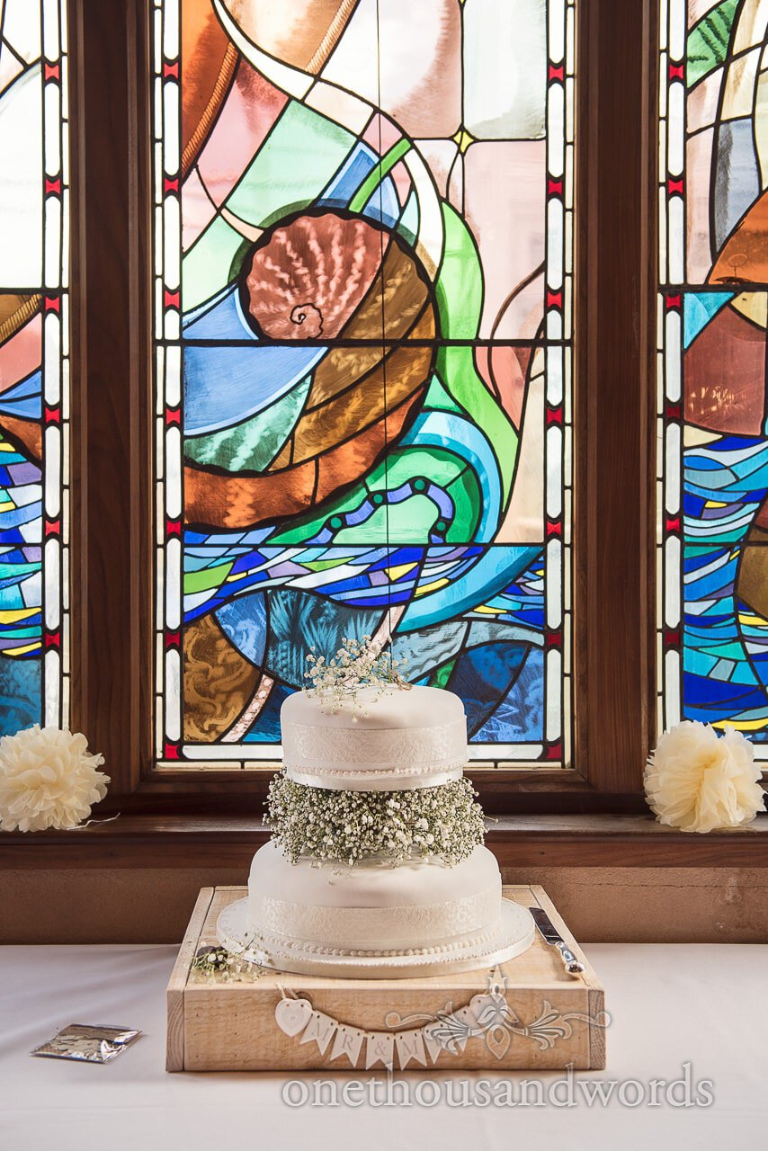 Wedding cake in stained glass window at Scaplens court wedding photographs