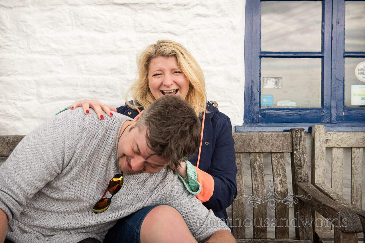 Wedding couple laughing on wooden bench at Dorset pub engagement photo shoot