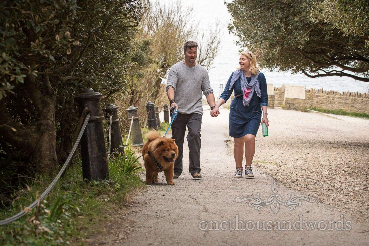 Wedding couple with chow chow dog walk past London street bollards at Durlston Castle country park