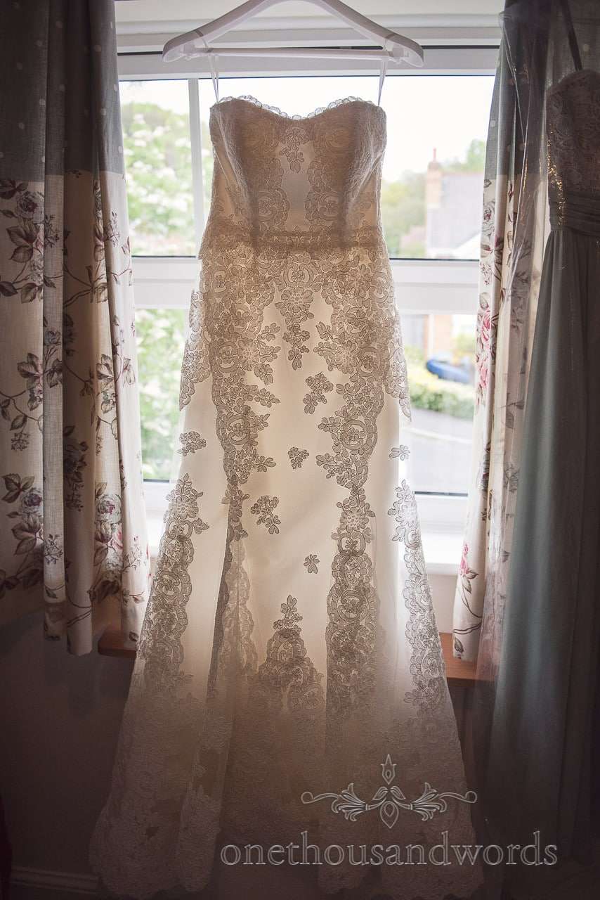 Wedding dress hangs in window on morning of Scaplens Court wedding photographs