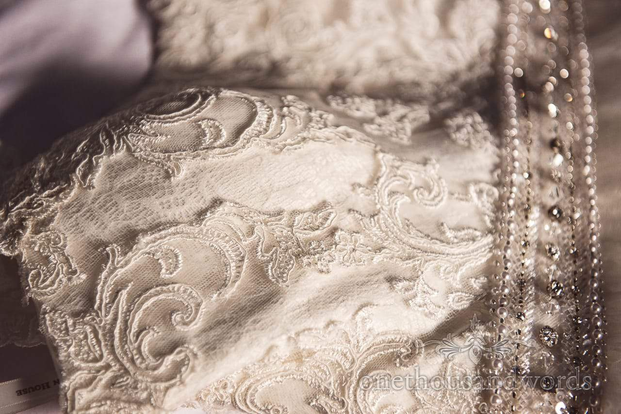 Appliqué and beaded detailing close up photograph of wedding dress in natural light