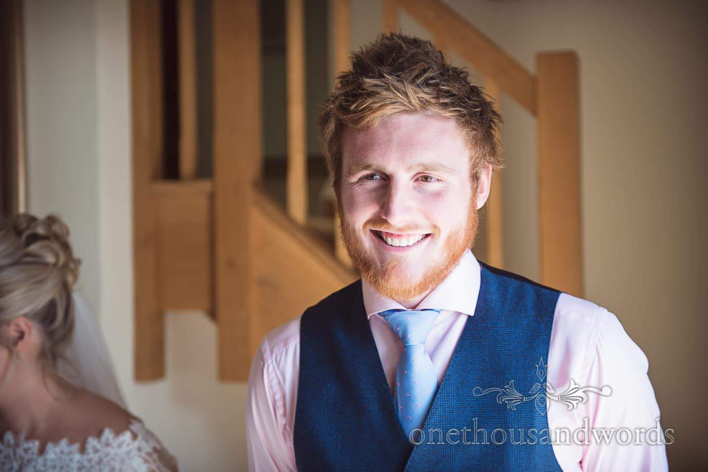 Bearded groom with pink shirt and blue waistcoat smiles during receiving line