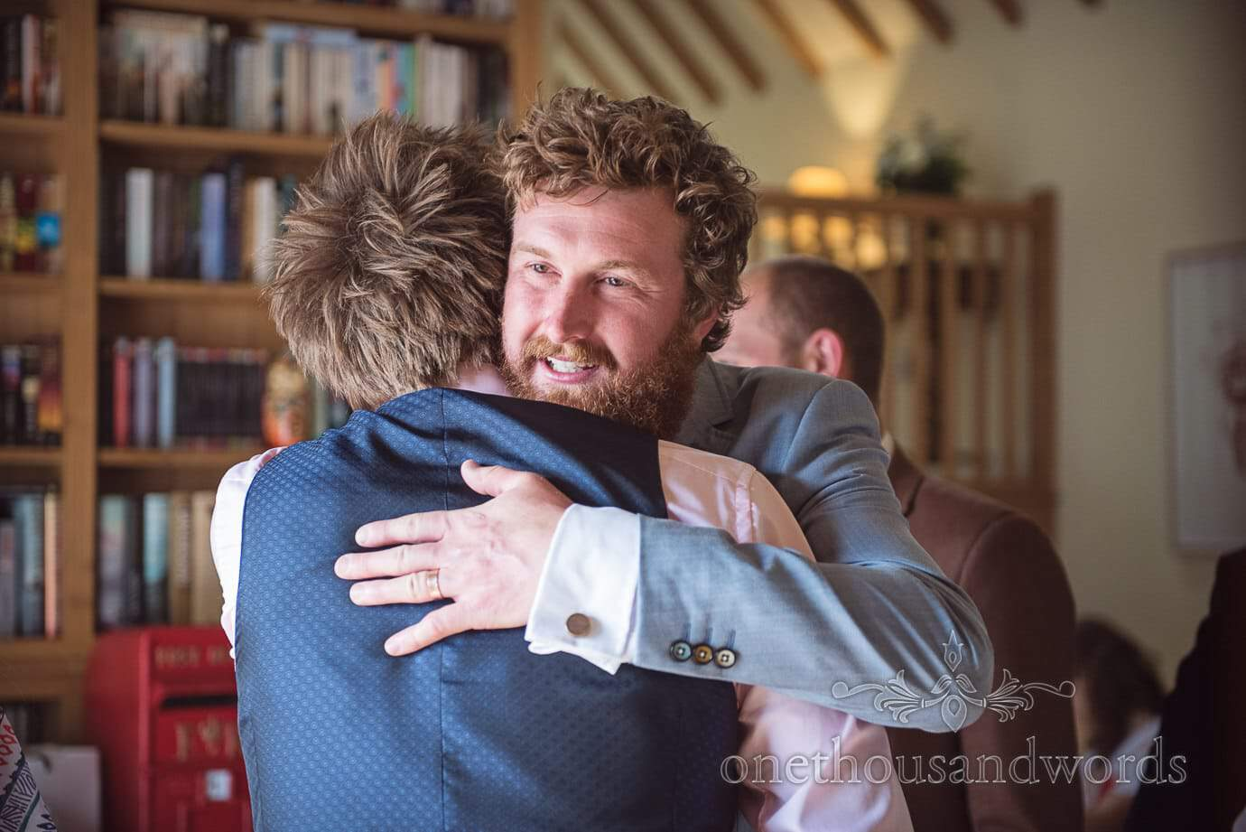 Bearded wedding guest in pale blue suit with multicoloured buttons hugs groom