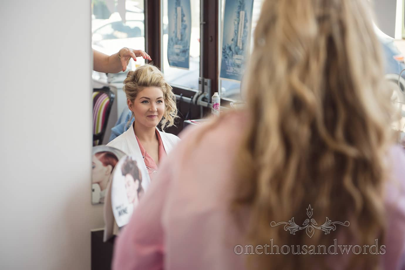 Beautiful blonde bride has wedding hair styled in mirror on morning of country wedding