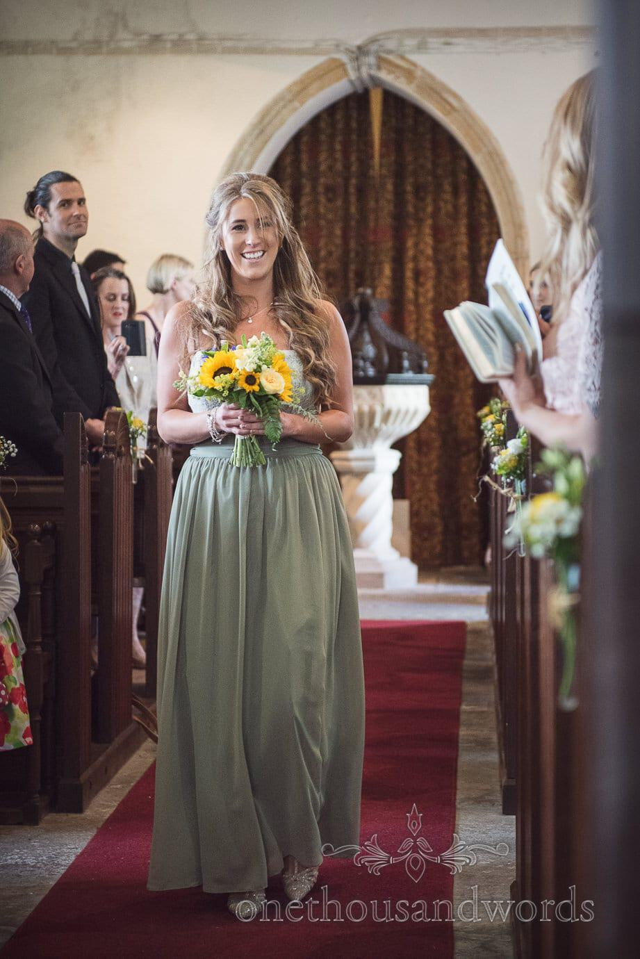 Beautiful blonde bridesmaid in green smiles as she walks own church aisle in Dorset