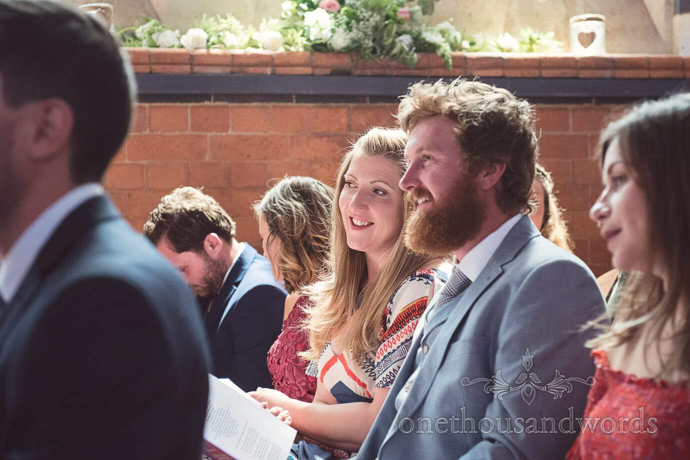 Beautiful blonde wedding guest smiles during church wedding ceremony