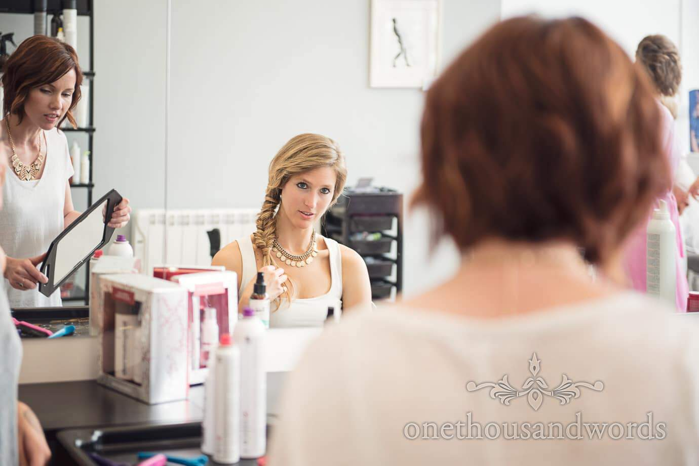 Beautiful blonde wedding guest with fishtail hair at bridal preparations in beauty salon