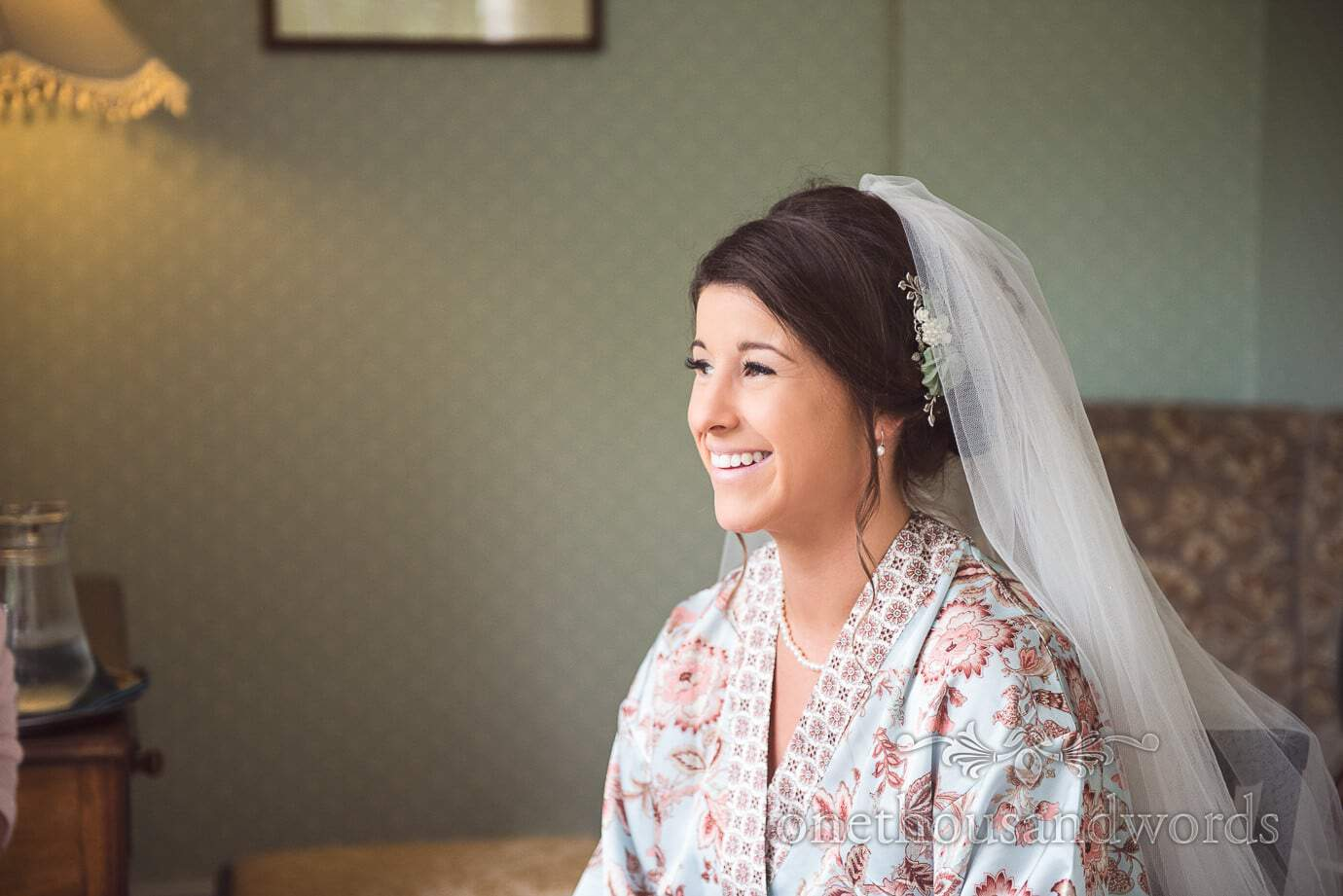 Beautiful bride in silk dressing gown and veil during wedding morning preparations