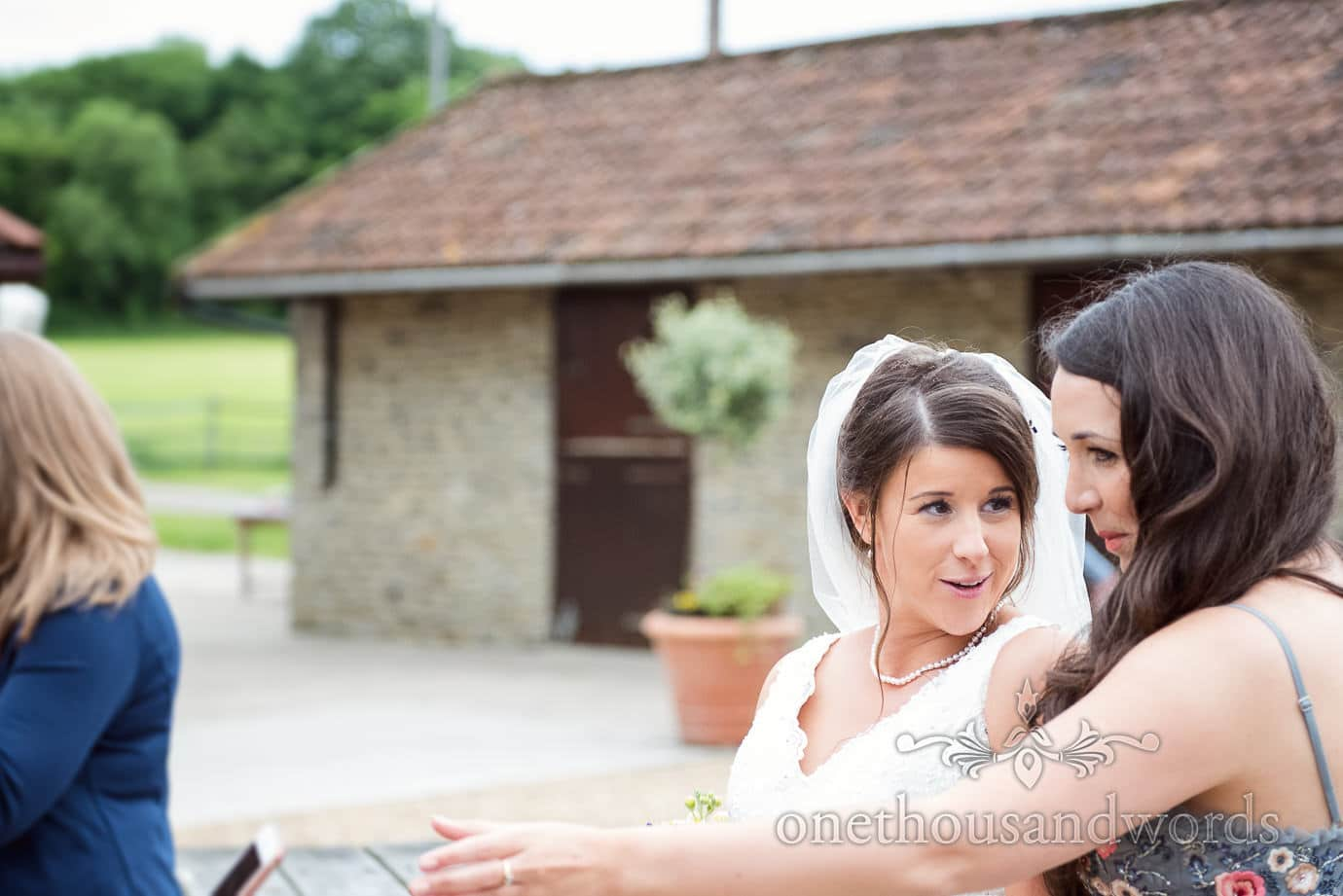 Beautiful bride with pearls and veil talks to wedding guests at rustic wedding venue in Dorset