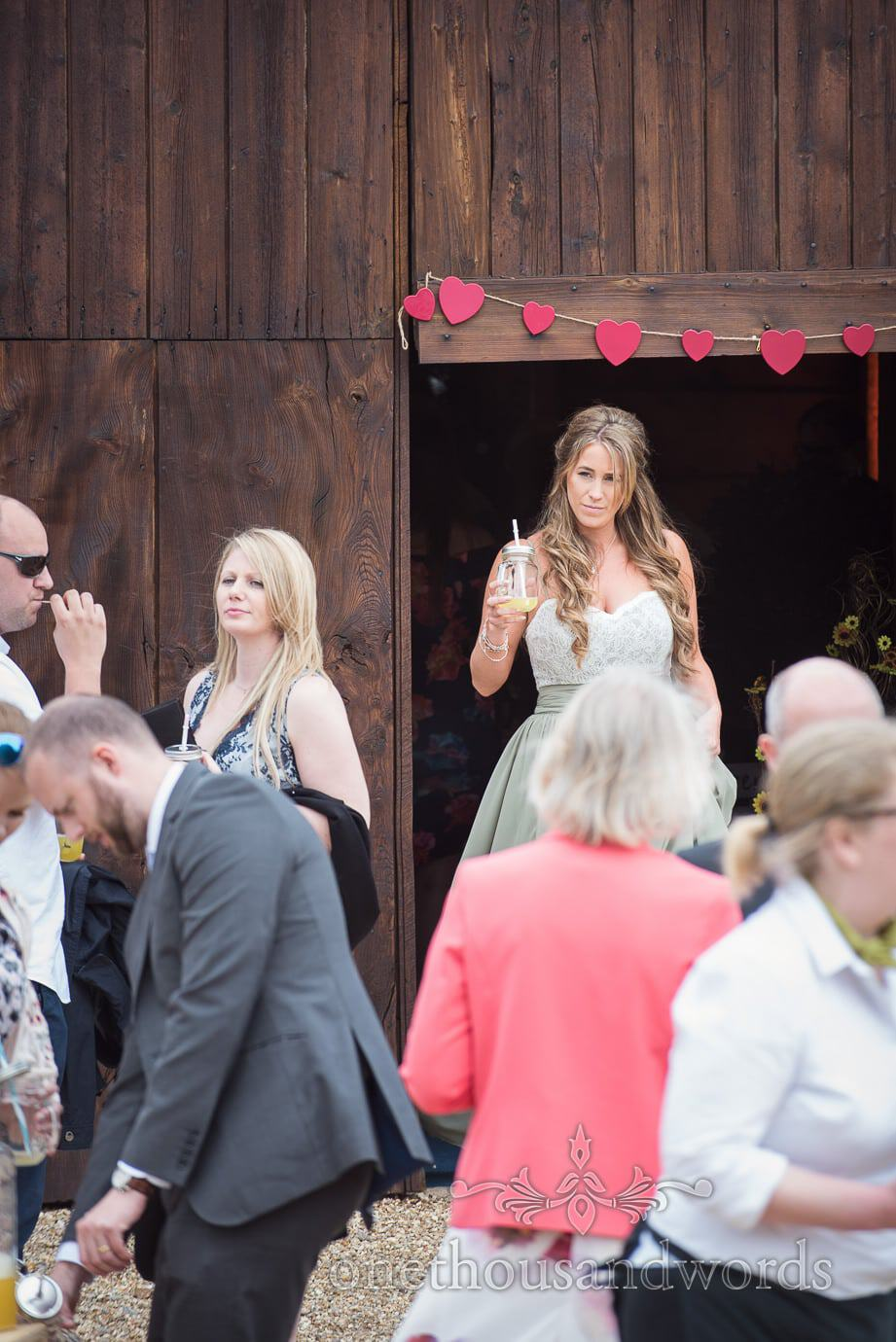 Beautiful bridesmaid exits rustic wedding wooden barn door with red love heart bunting