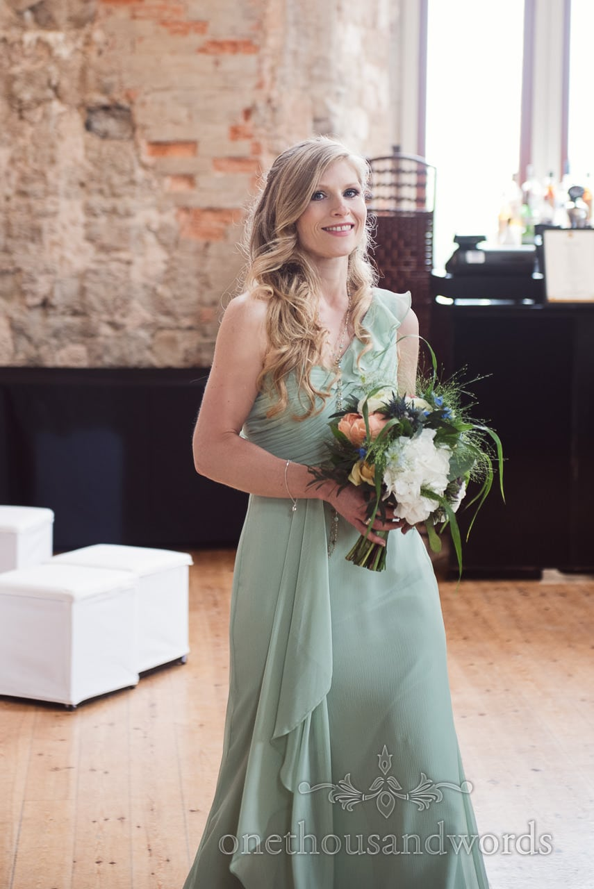 Beautiful bridesmaid in dusty green bridesmaids dress carries blue orange and white wedding bouquet