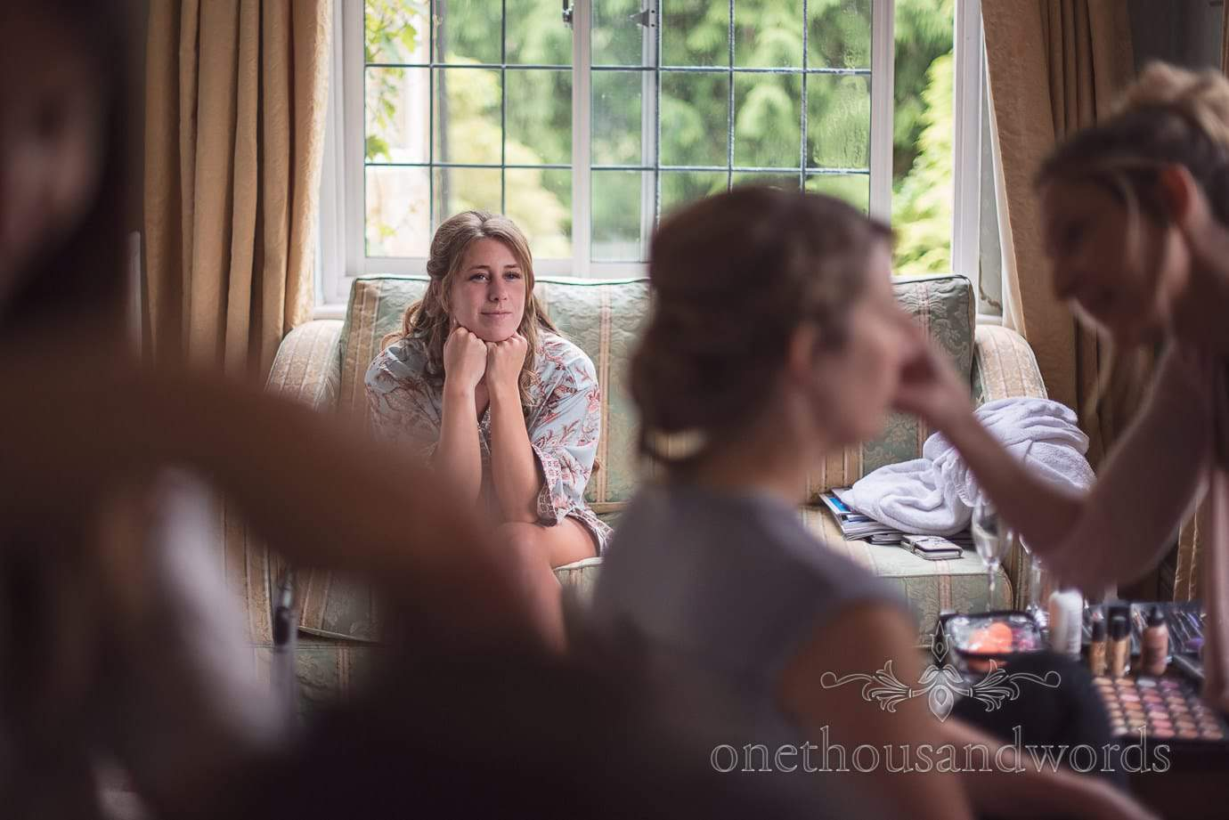 Beautiful bridesmaid watches wedding make up artist on wedding morning at Hotel