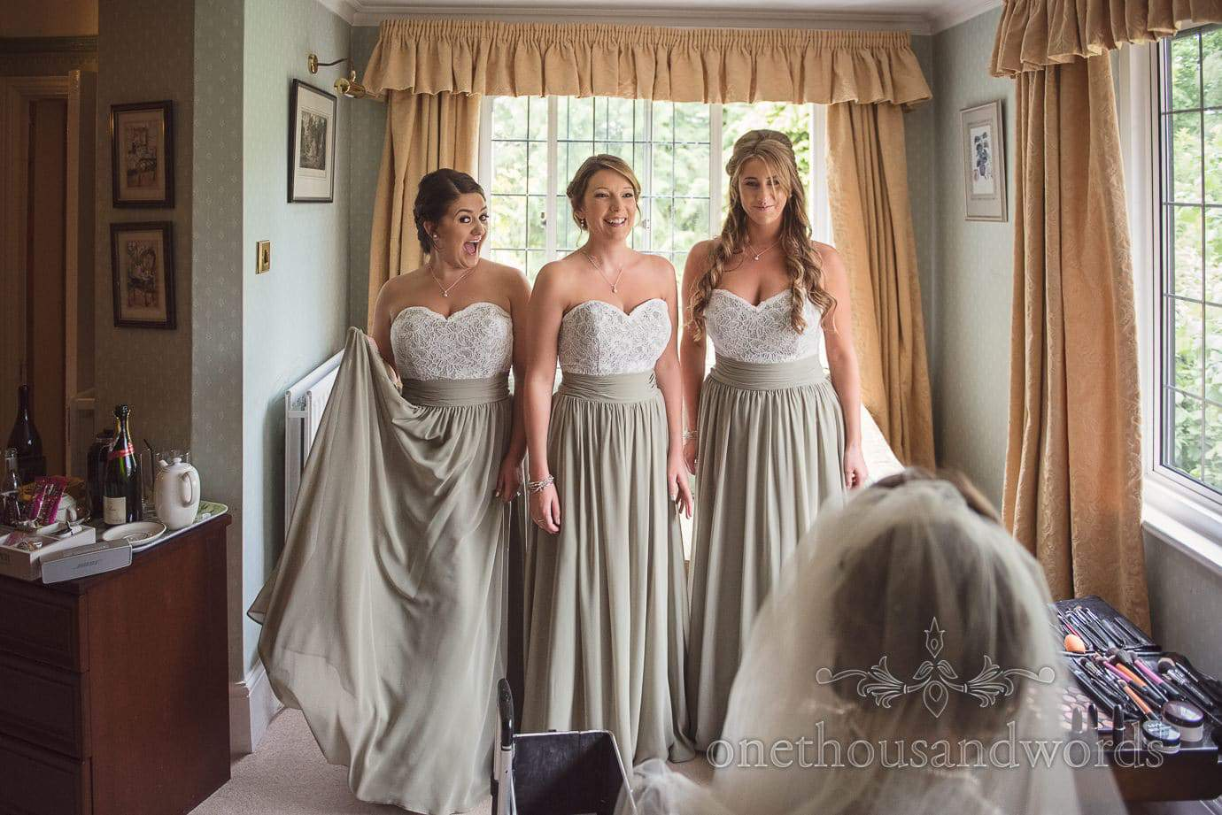 Beautiful bridesmaids in dusty green bridesmaids dresses with white lace detailing