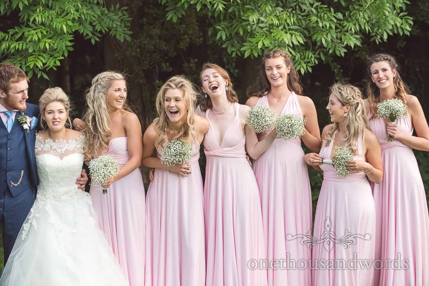 Beautiful bridesmaids in dusty pink Greco-Roman bridesmaids dresses with gypsophila bouquets