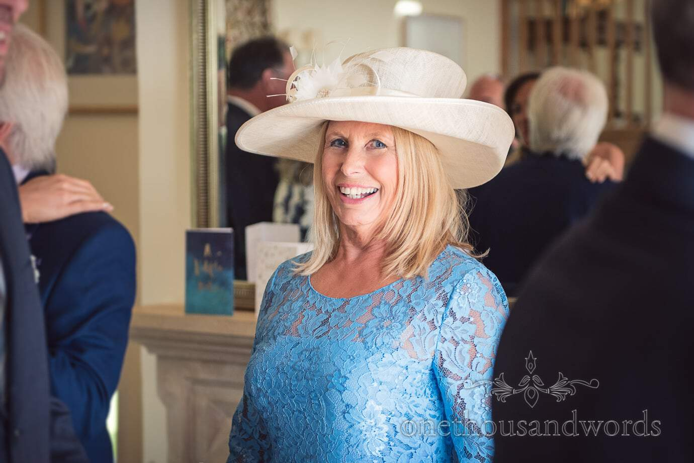 Beautiful mother of the bride in sky blue detailed dress and white wedding hat