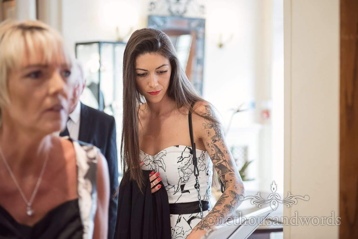 Beautiful Rock and Roll wedding guest with tattoo sleeve and black and white dress