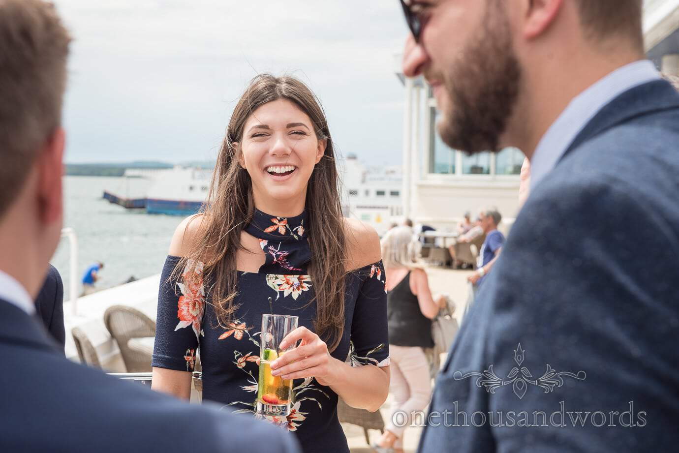 Beautiful wedding guest laughing at wedding drinks reception by the sea with ferry in background