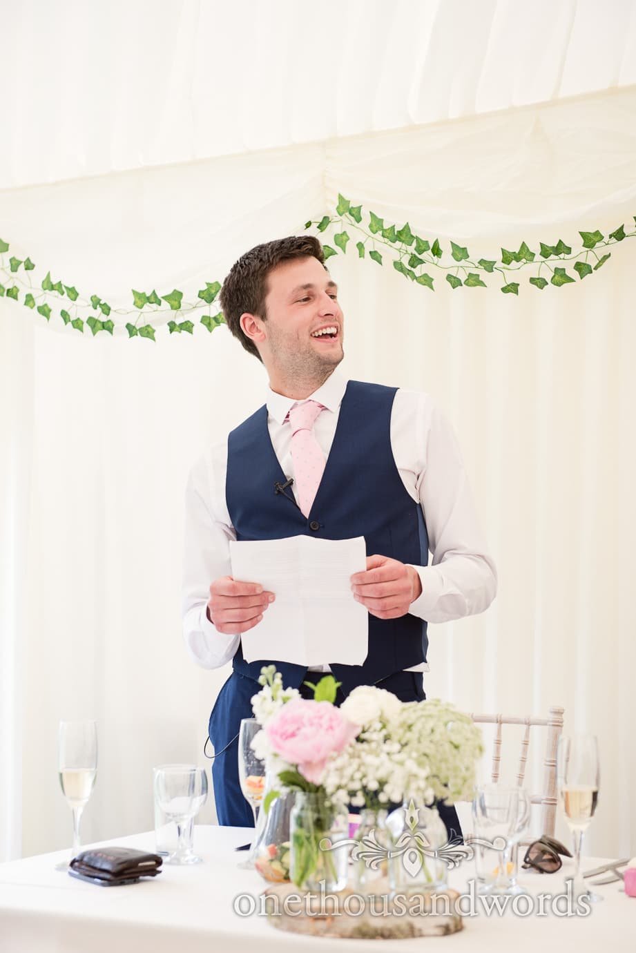 Best man makes wedding speech at country wedding marquee with flowers and ivy