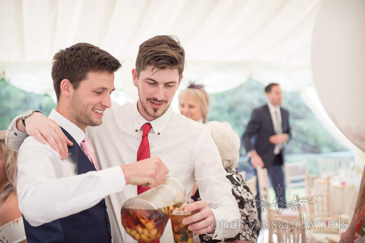 Best man pours wedding Pims at countryside marquee wedding breakfast