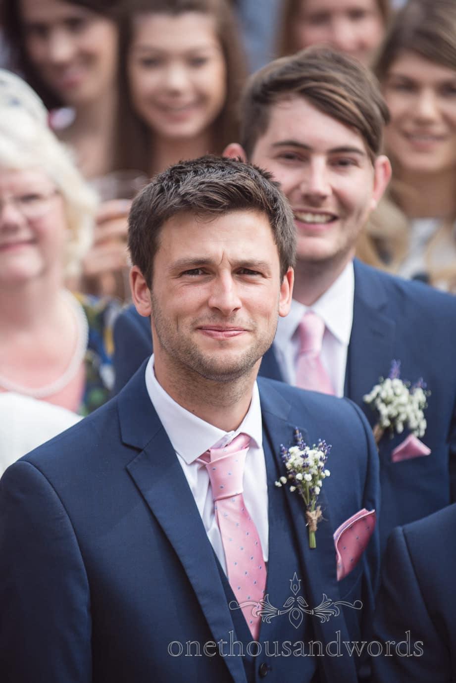 Best man wears three piece blue wedding suit with matching pink handkerchief and tie