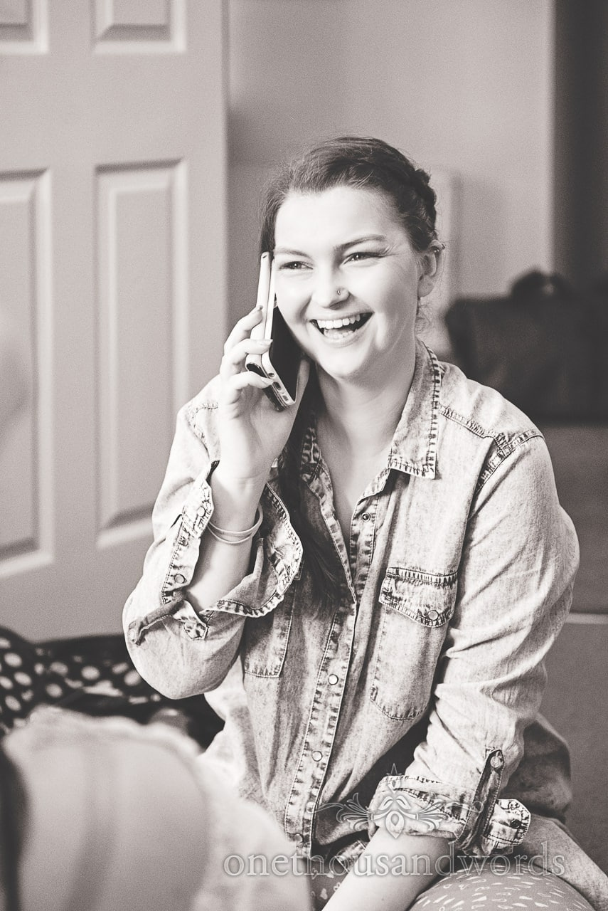 Black and white bridal preparation photograph of bride laughing on phone