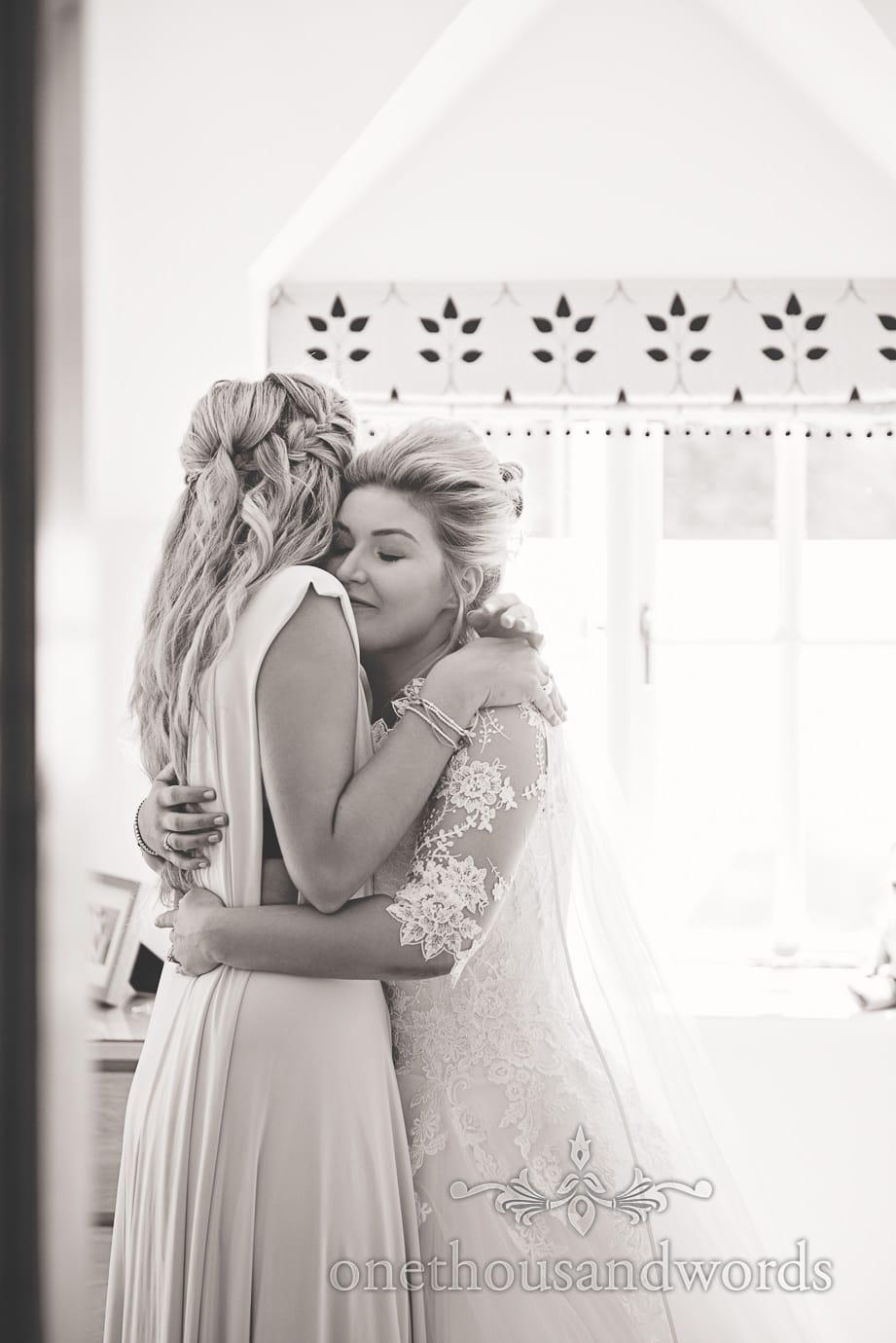 Black and white documentary wedding photograph of bride hugging bridesmaid on wedding morning