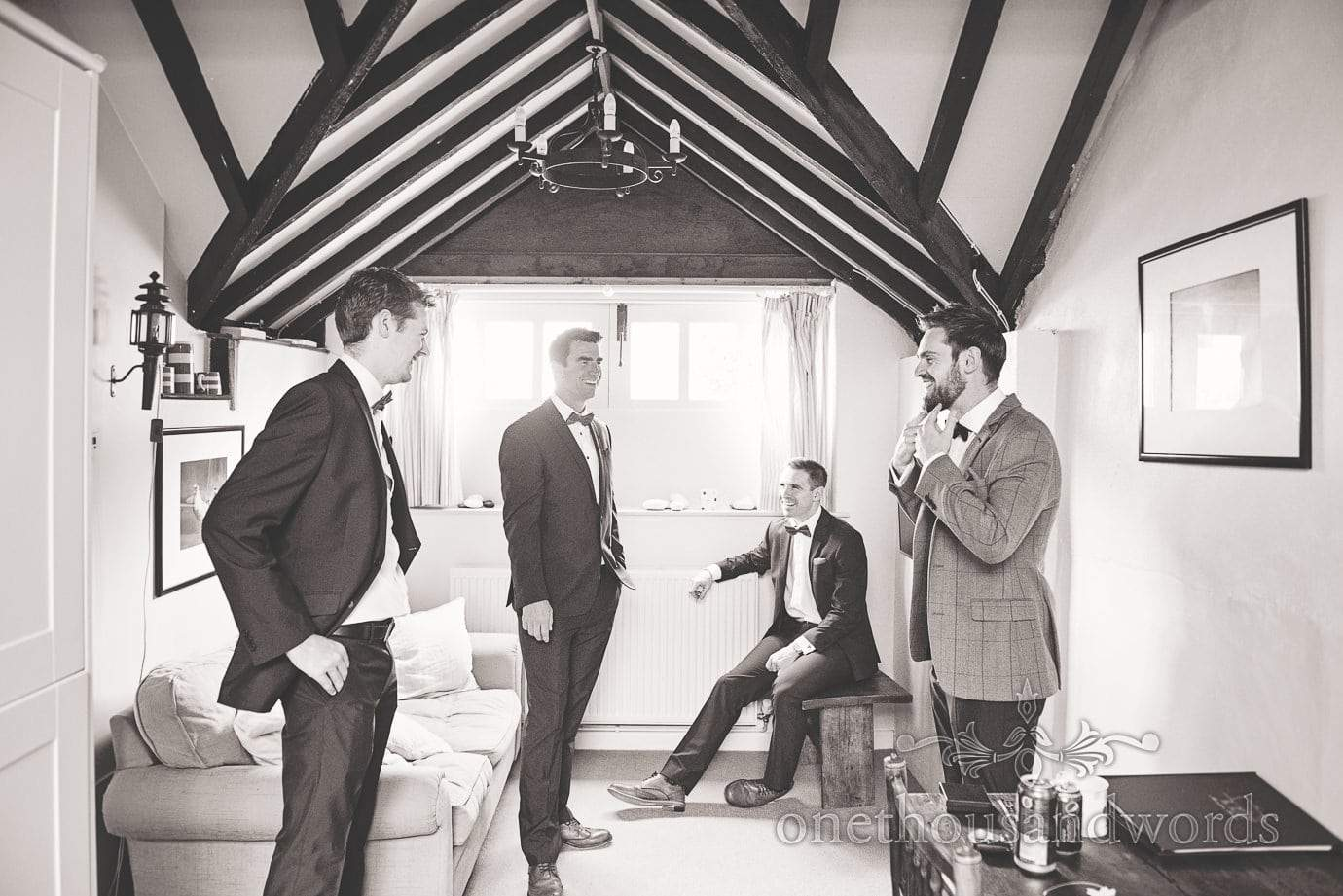 Black and white documentary wedding photograph of groom preparations in Dorset