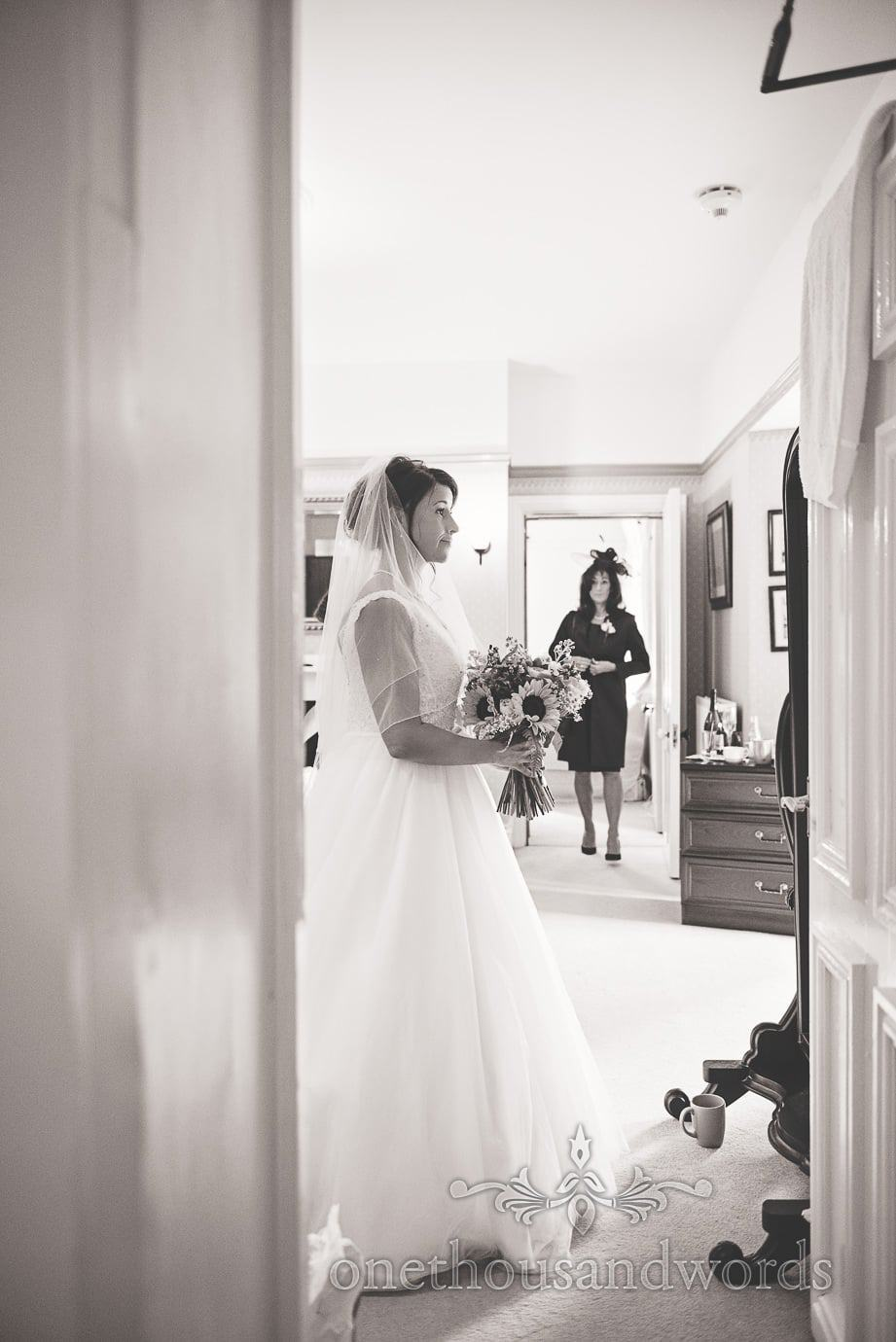 black and white photo of bride looking in mirror as mother of the bride watches in background
