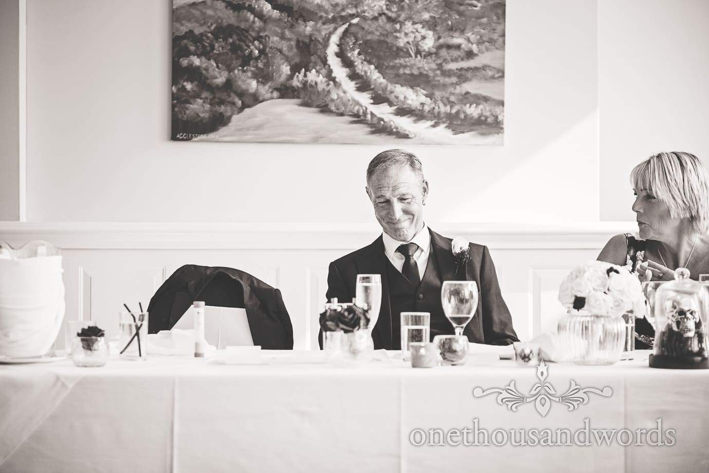 Black and white photograph of father of the groom listening to wedding speeches