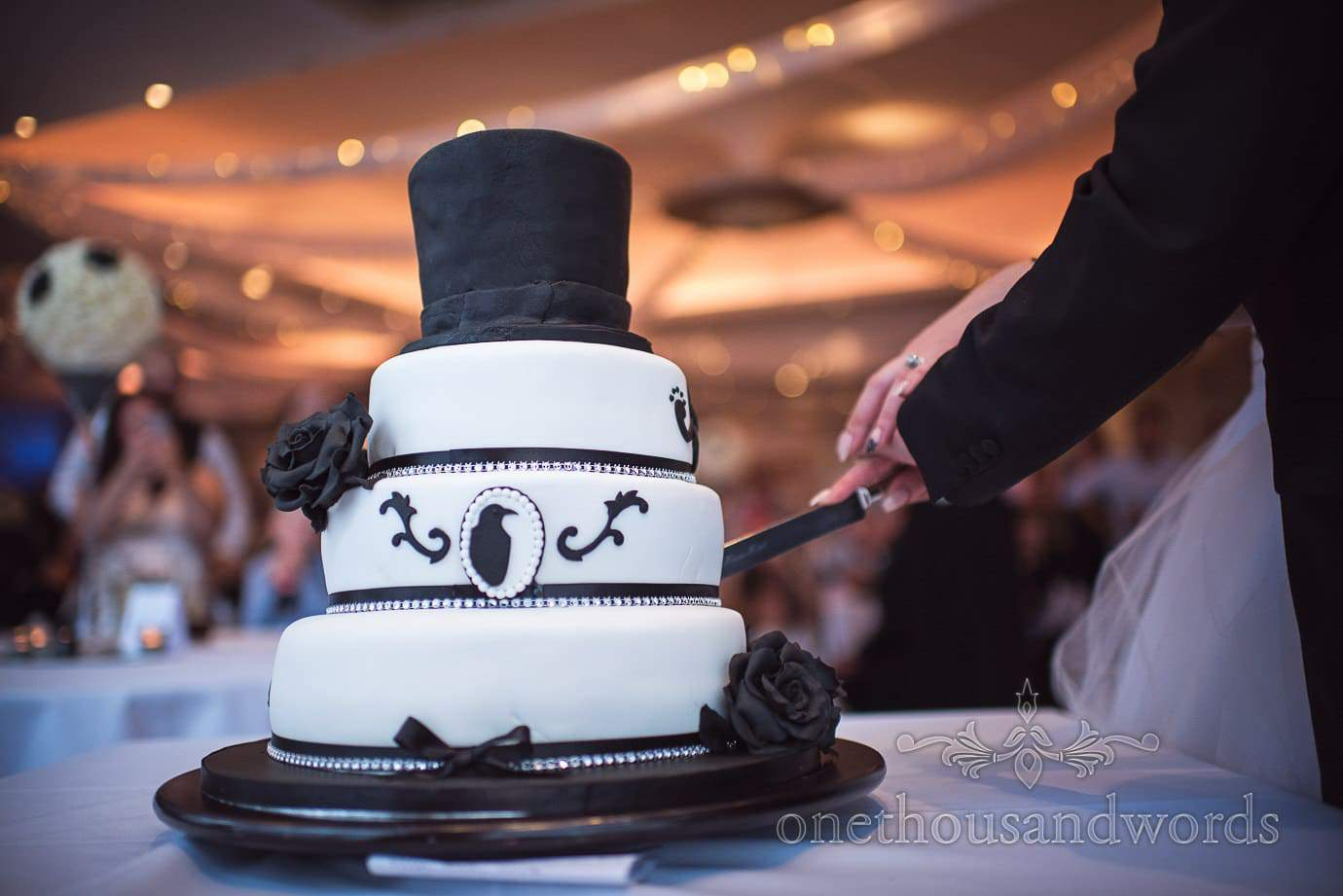 Black and white rock and roll themed wedding cake with black roses and top hat