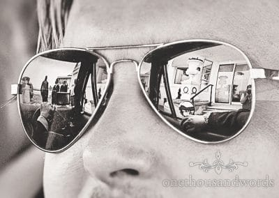 Black and white sunglasses reflection of groom driving The General Lee wedding car
