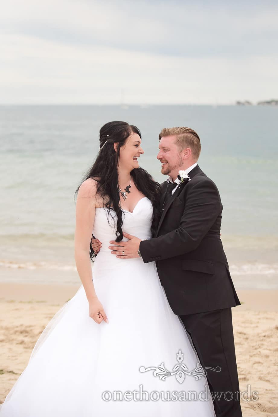 Black and white themed wedding bride and groom on the beach with the Dorset sea