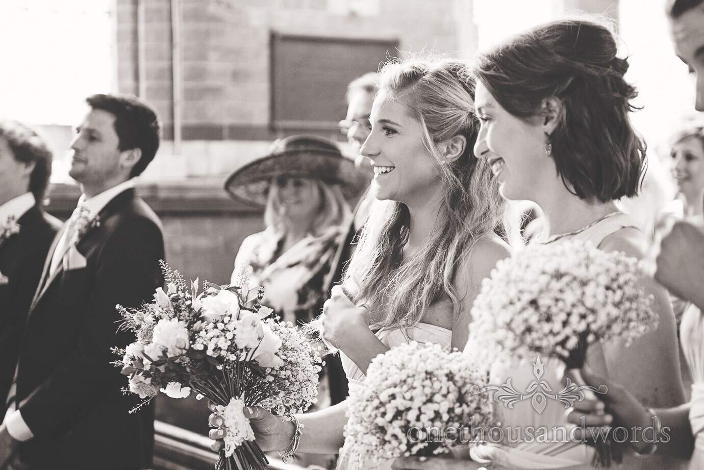 Black and white wedding photograph of beautiful bridesmaids at church ceremony